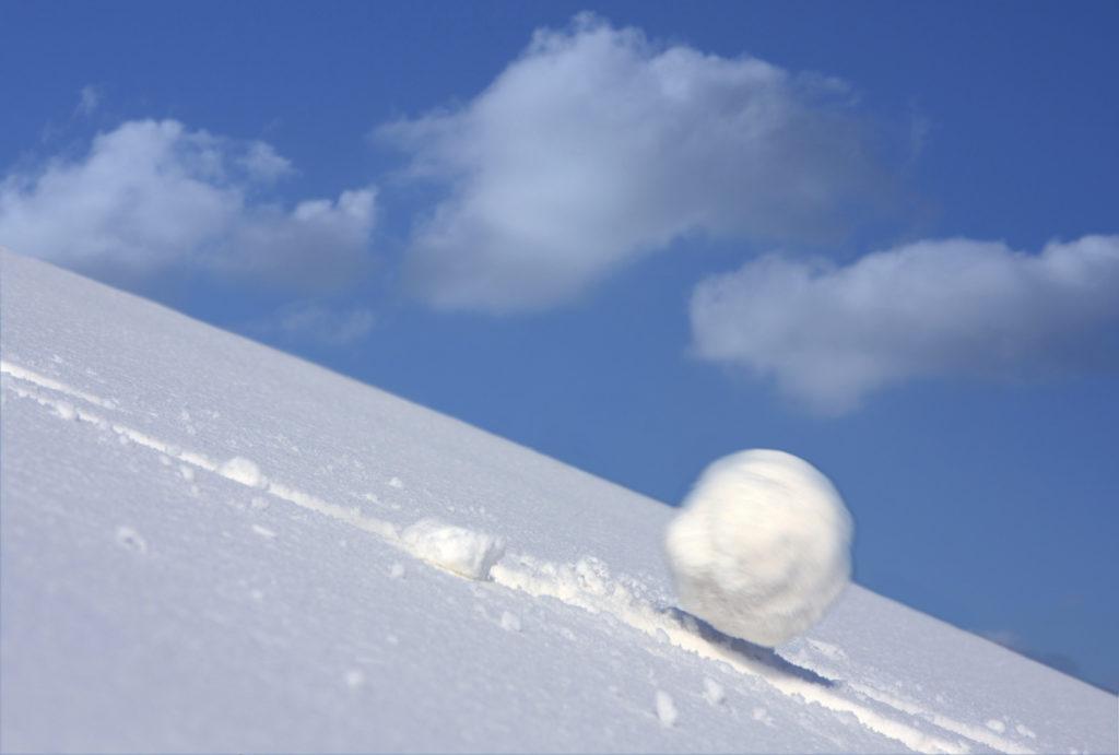 Снежный ком катится с горы и набирает скорость.